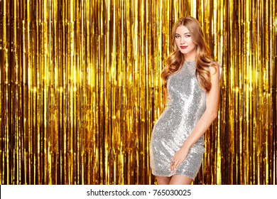 Beautiful Woman celebrating New Year and Christmas. Girl in glamorous Silver Dress. Girl posing over Golden sparkly background. Happy New Year. Holiday and Party