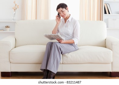Beautiful Woman with a cellphone and a newspaper in the living room