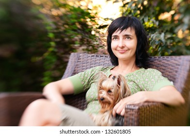 Beautiful woman in chair with little dog in garden relaxing outdoors