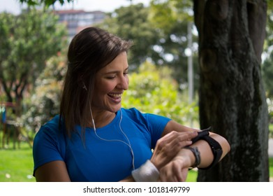 Beautiful woman checking application to run on her cell phone before starting to train