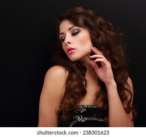 Beautiful woman with chic brown curly hair looking on black background