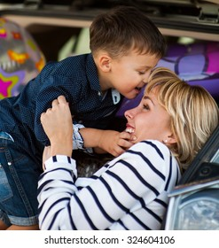 Beautiful woman with a child four years in the car are going to have a trip
