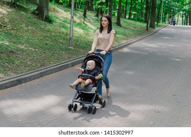 Beautiful woman with a child in a pram walks through a summer park.