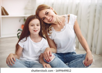 Beautiful woman with child. Woman in a white t-shirt. Little daughter in a bedroom