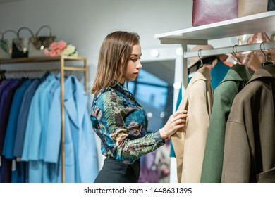 a beautiful woman chooses a coat in the store.