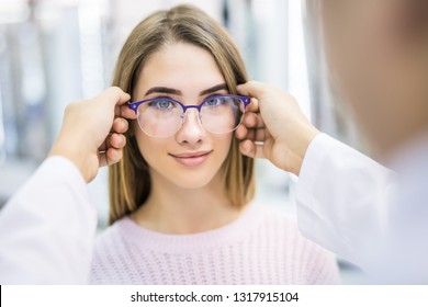 Beautiful woman choosing eyeglasses while male oculist standing near with another eyeglasses in ophthalmic shop