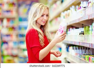beautiful woman choosing personal care product in supermarket