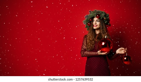 Beautiful woman with Christmas spruce fir wreath with cones and new year decoration balls on red background. Banner