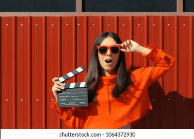 Beautiful Woman with Cinema Clapper on Red Background. Cool model girl with film slate at casting audition