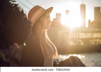 Beautiful woman in the city pier looking to the side smiling at sunset time