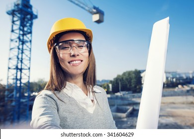 Beautiful woman civil engineer is taking a self portrait in her work in front of a crane