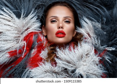 Beautiful woman with classic holiday make-up, red lips, curls in a multi-colored llama coat. Beauty face. Photo taken in studio