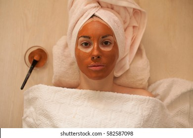 Beautiful woman with a clay or a mud mask on her face. pink clay. copy space. beauty salon