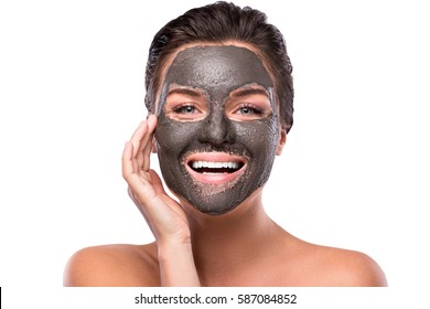 Beautiful woman with a clay or a mud mask on her face over white background