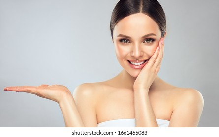 Beautiful woman with  clean fresh skin .Sweet smiling girl  expressive  pointing to the side . Presenting your product. . Expressive facial expressions.  Cosmetology , beauty  and spa .  Face care