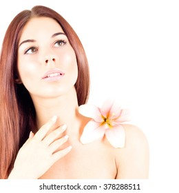 Beautiful woman with clean skin and with flower looks up. Facial result.