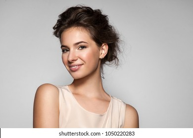 Beautiful  woman with clean skin, natural make-up in a beige dress on grey background