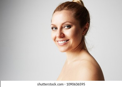 Beautiful woman with clean skin, natural make-up, and white teeth on grey studio background.Medical and cosmetic facial skin healthcare concept.Copy paste space