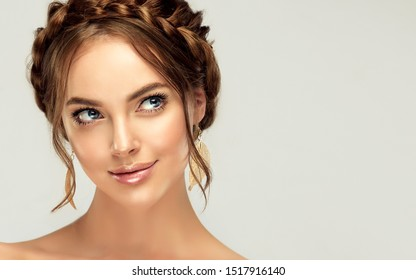 Beautiful woman with clean skin on her face. Girl model with braided braid around her head. Hairstyle in the trend. Beauty, cosmetics and cosmetology. Fashion earrings as accessories
