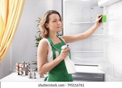 Beautiful woman cleaning empty refrigerator in kitchen