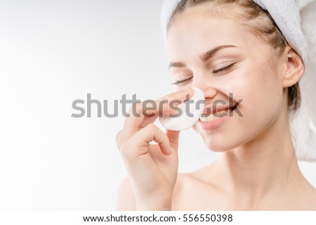 Beautiful woman cleaning her face with cotton swab - over white background and smiling