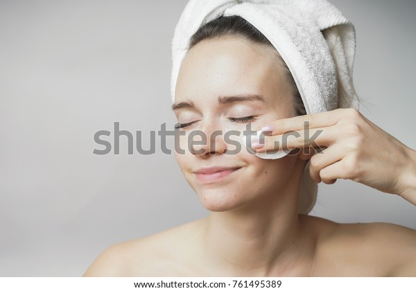 Beautiful woman cleaning her face with cotton swab  under eyes