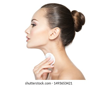 Beautiful woman cleans the neck with cosmetic cotton swab.