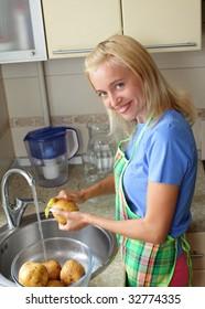 Beautiful woman cleans a potato on kitchen