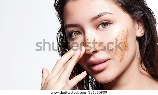 Beautiful woman cleans the skin scrub on a white background isolated