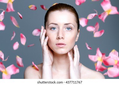 beautiful woman with clear skin and falling rose petals at grey background
