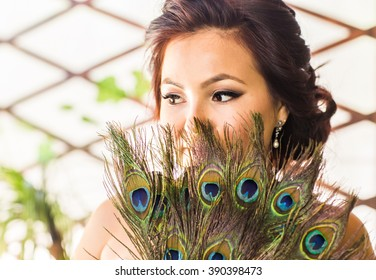 Beautiful woman  close up with  fan made of peacock feather