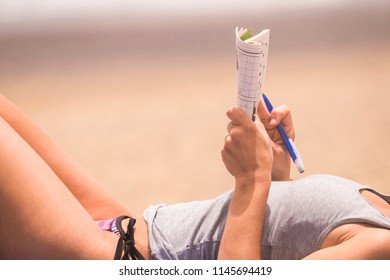 beautiful woman close up on body relaxed and hae nice time doing a words play on paper. beach vacation leisure activity under the sunlight. skin tanner concept in holiday outdoor activity for lady