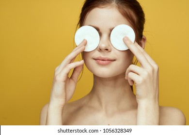 beautiful woman closes her eyes with cotton pads