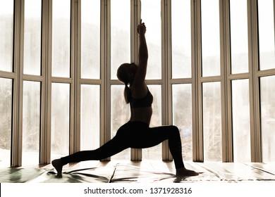 Beautiful woman coach yoga practice. Yoga concept. Warrior pose - Virabhadrasana