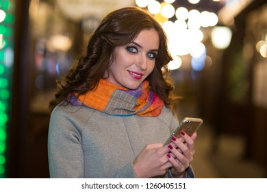 Beautiful woman in a coat and scarf walks in the evening city with garlands and light bulbs