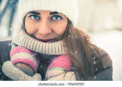 Beautiful woman at cold and snowy winter walking at New York city. Warmly dressed in a coat with a hat.