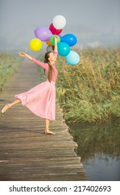 Beautiful woman with colorful balloons dancing on wooden bridge road early in foggy morning