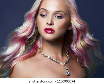 beautiful woman with Colorful hair and Jewelry. Rainbow Hairstyles. Beauty Fashion Model with Colorful Dyed Hair