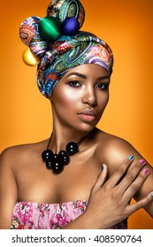 Beautiful woman colorful portrait. Young afro girl posing on yellow background with colorful  material on head. Ethnic style.