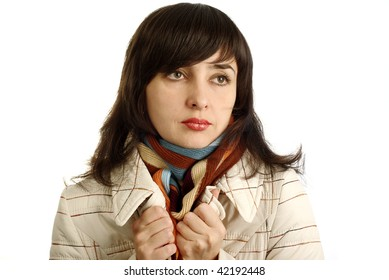 Beautiful woman in colorful scarf and beige coat getting cold. Isolated on white.