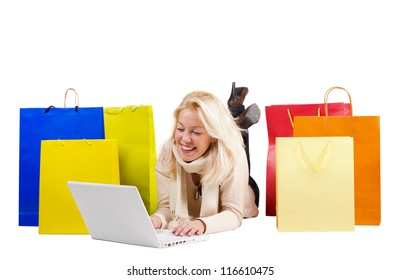 Beautiful woman with colorful shopping bags and a laptop