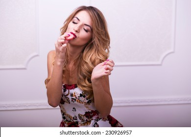 Beautiful woman in colour dress eating macaroons in studio