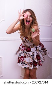Beautiful woman in colour dress make faces with macaroons in studio