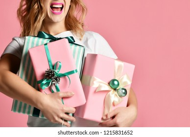 Beautiful woman composition hold pink and pastel green Christmas presents gifts for new year celebration smiling under snow on pink background