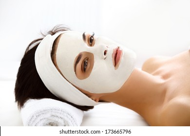 Beautiful Woman With Cosmetic Mask on Face. Girl Gets Treatment in Spa Salon against white Background