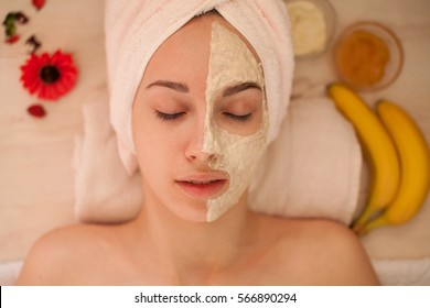 Beautiful Woman With Cosmetic Mask on Face. Girl Gets Treatment in Spa Salon against white Background. Homemade mask for face. spa treatments