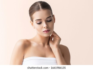 Beautiful woman cosmetic natural make up hand touching skin beauty model face pink background
