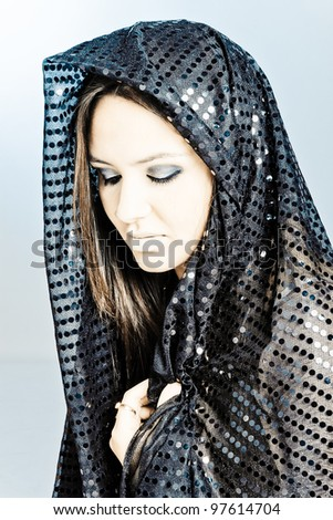d63c2048278 Beautiful woman covering her face with a black hijab with beautiful bright  spots on it.