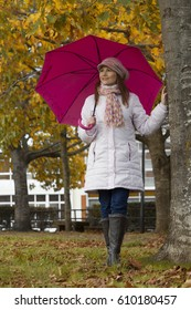Beautiful woman covering herself with her umbrella in the park on a rainy and cold autumn day.