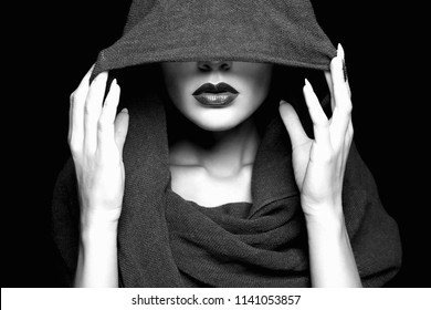 beautiful woman covers her face under hood. part of female face. Black and white portrait